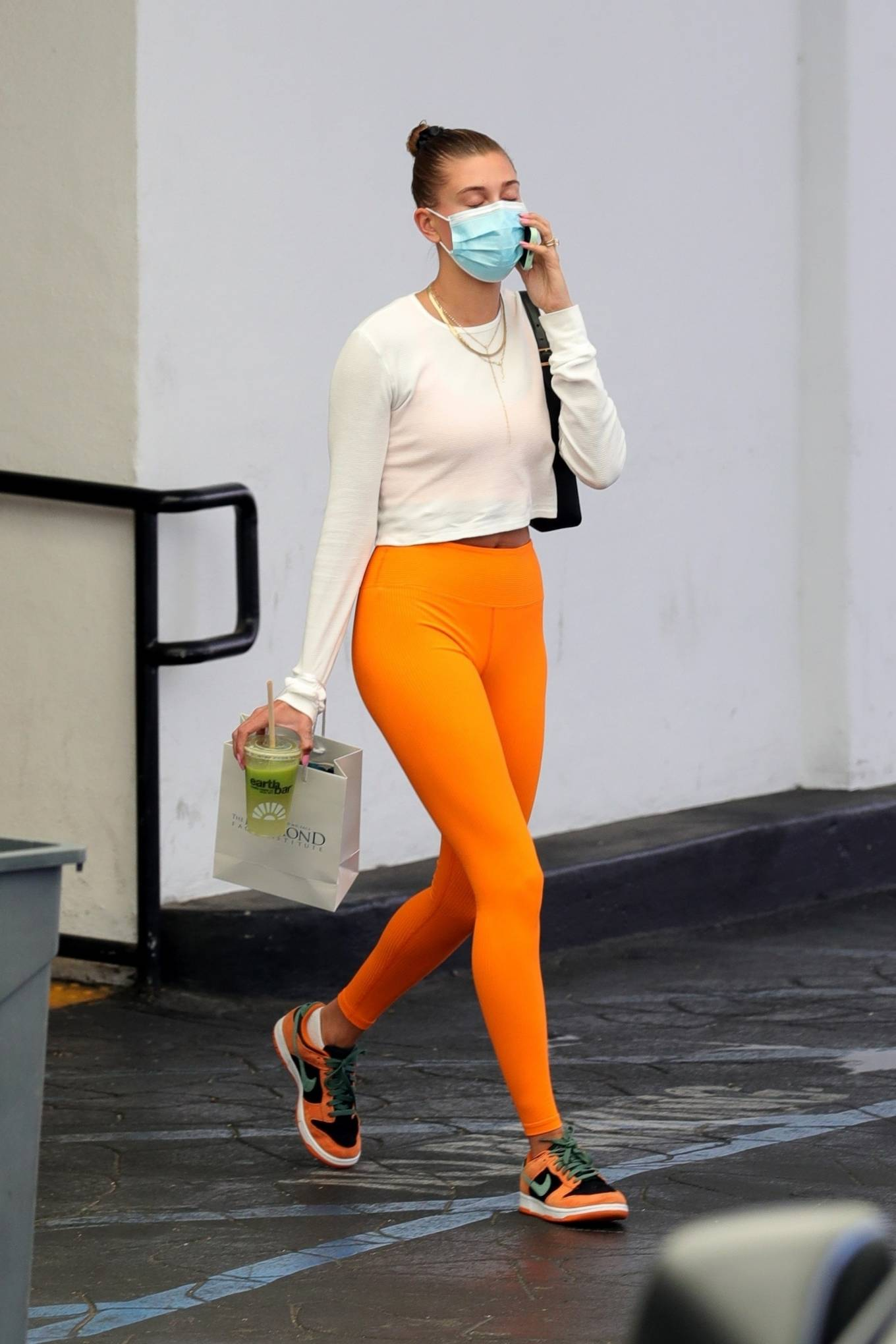 Hailey Baldwin rocking brand logo orange Nike lace-up sneakers