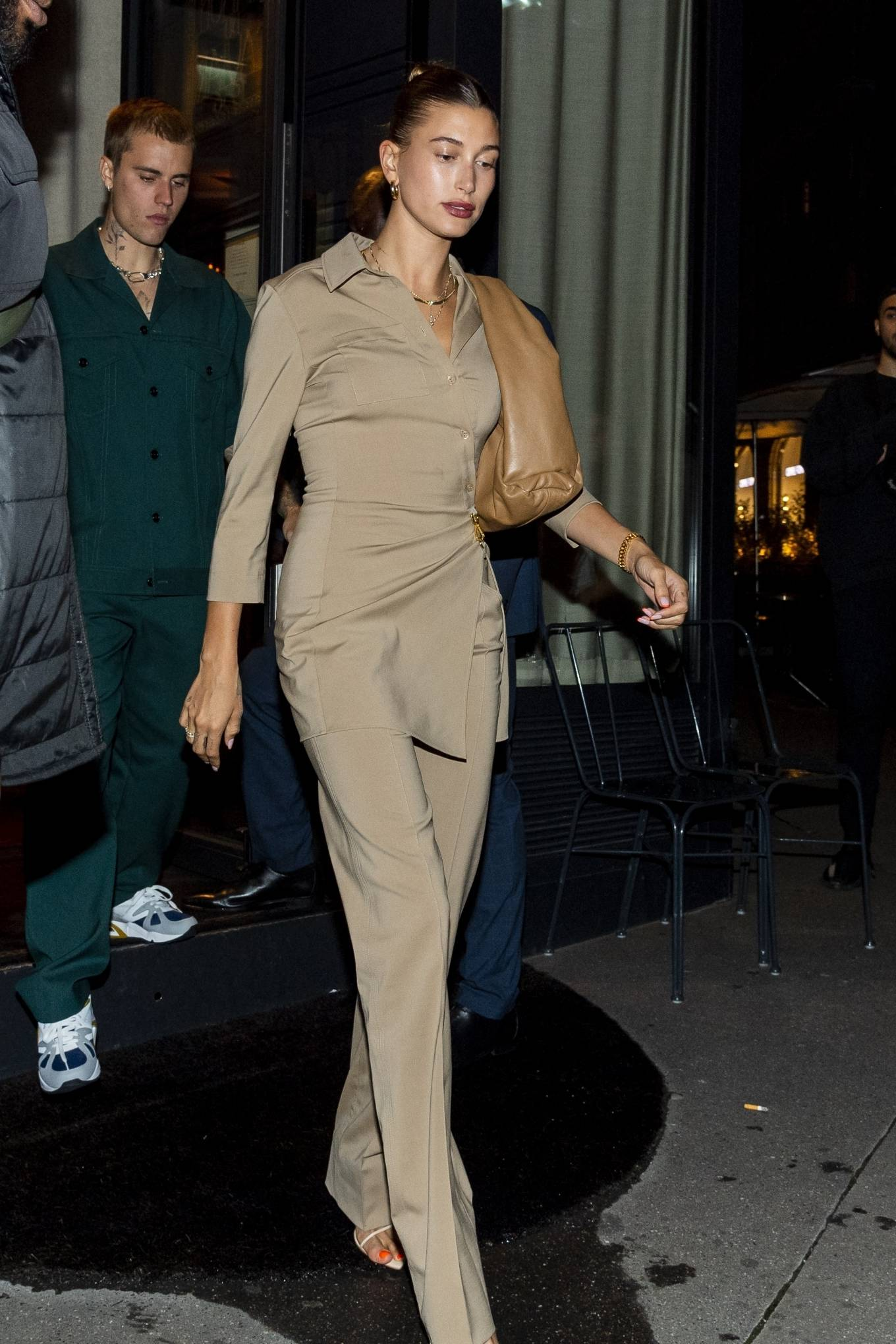 Hailey Bieber rocking a close fitting beige shirt with 3/4 sleeves, shirt collar and asymmetric design