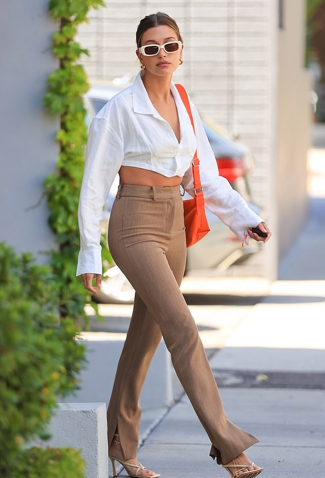 Hailey Baldwin rocking straight fit beige polyester mid rise trousers while out and about in LA