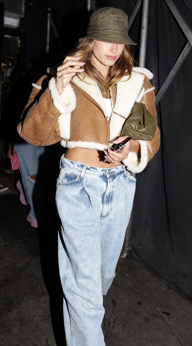 Hailey Bieber donning round white Nike lace-up sneakers with flat heel
