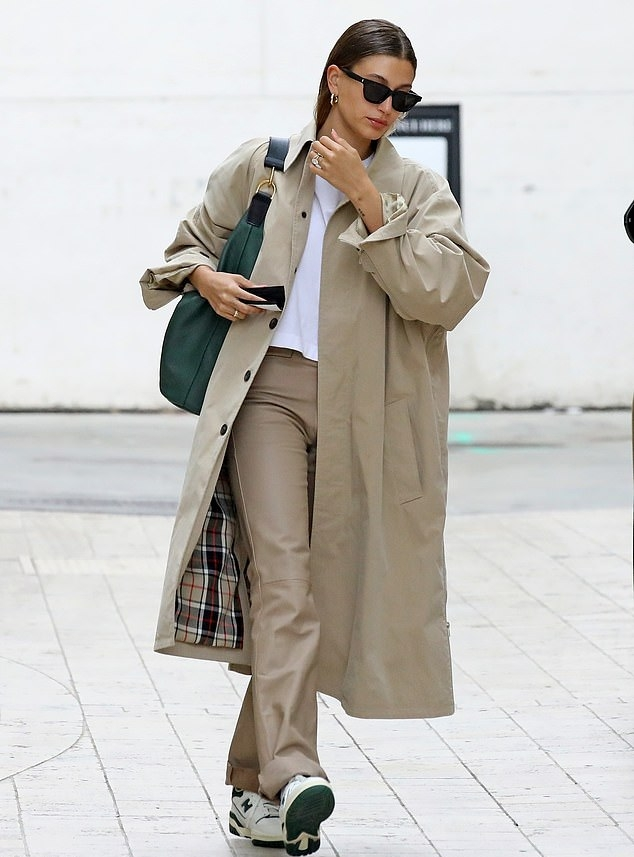 Hailey Bieber wearing a beige open front Balenciaga woolen trench coat with rolled sleeves, spread collar and button front while out and about in LA