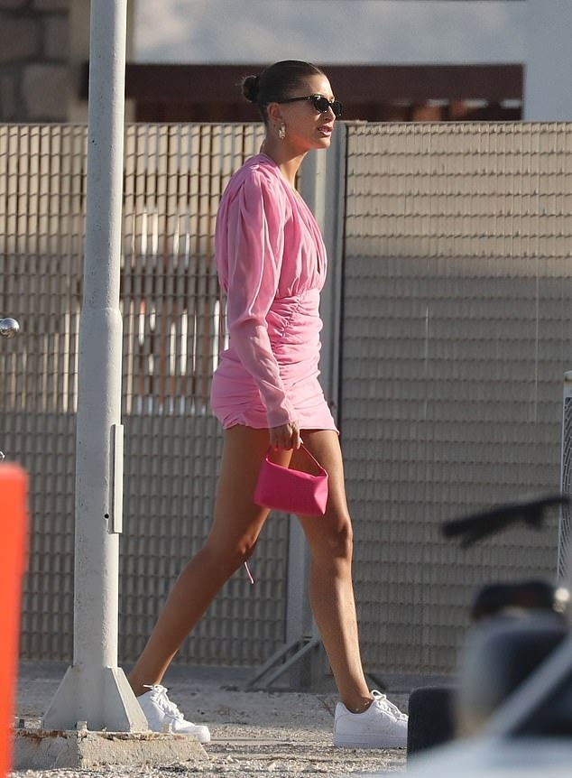 Hailey Baldwin, Nike sneakers, white sneakers, leather, figure hugging dusky pink Magda Butrym dress, bright pink hand bag, flat heel, round, lace-up, black sunglasses. Hailey Baldwin donning round white Nike lace-up sneakers with flat heel