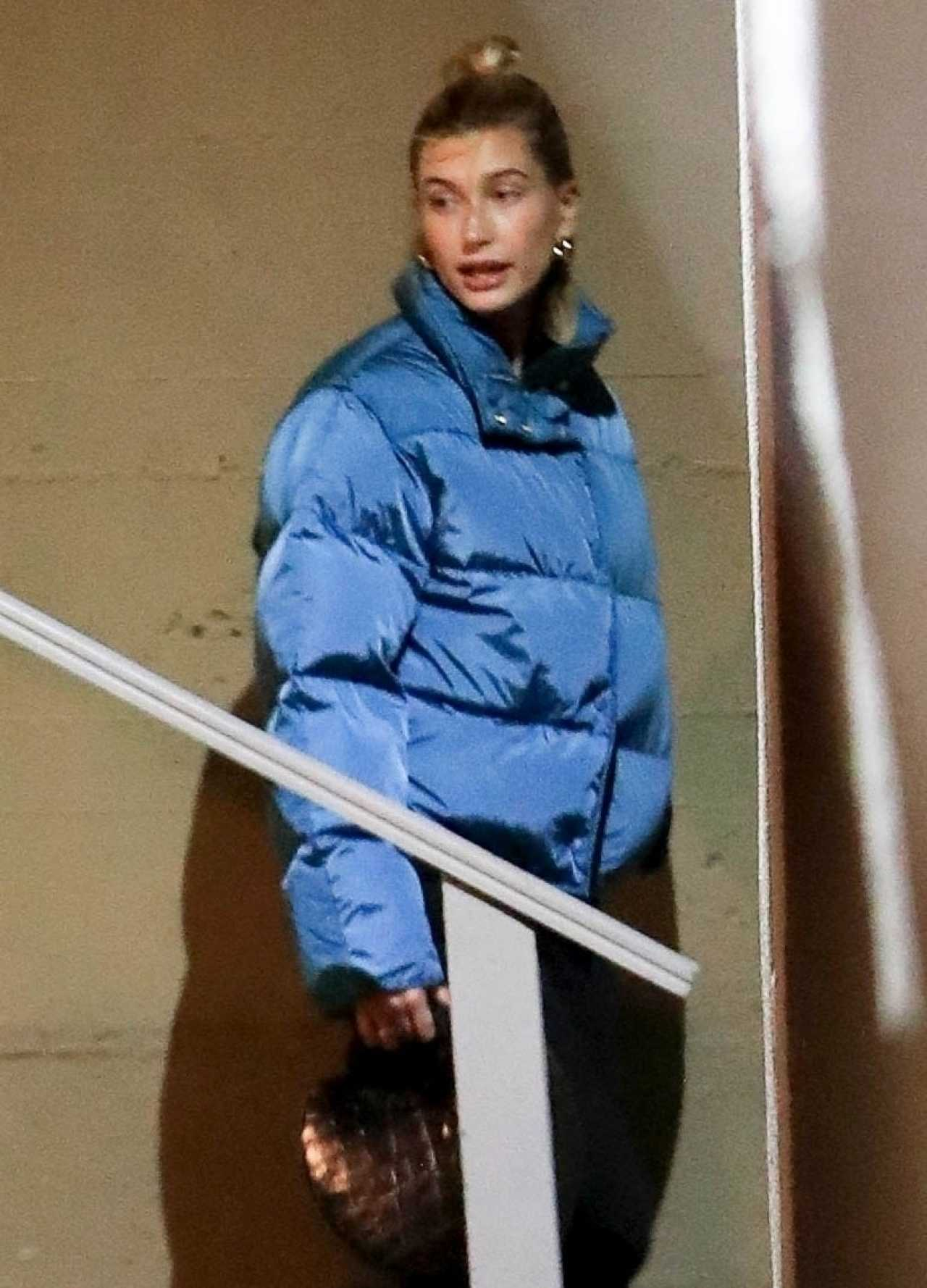 Hailey Bieber rocking a Oversized Acne Studios shiny blue nylon padded jacket with a nylon material, extra long sleeves and stand-up collar