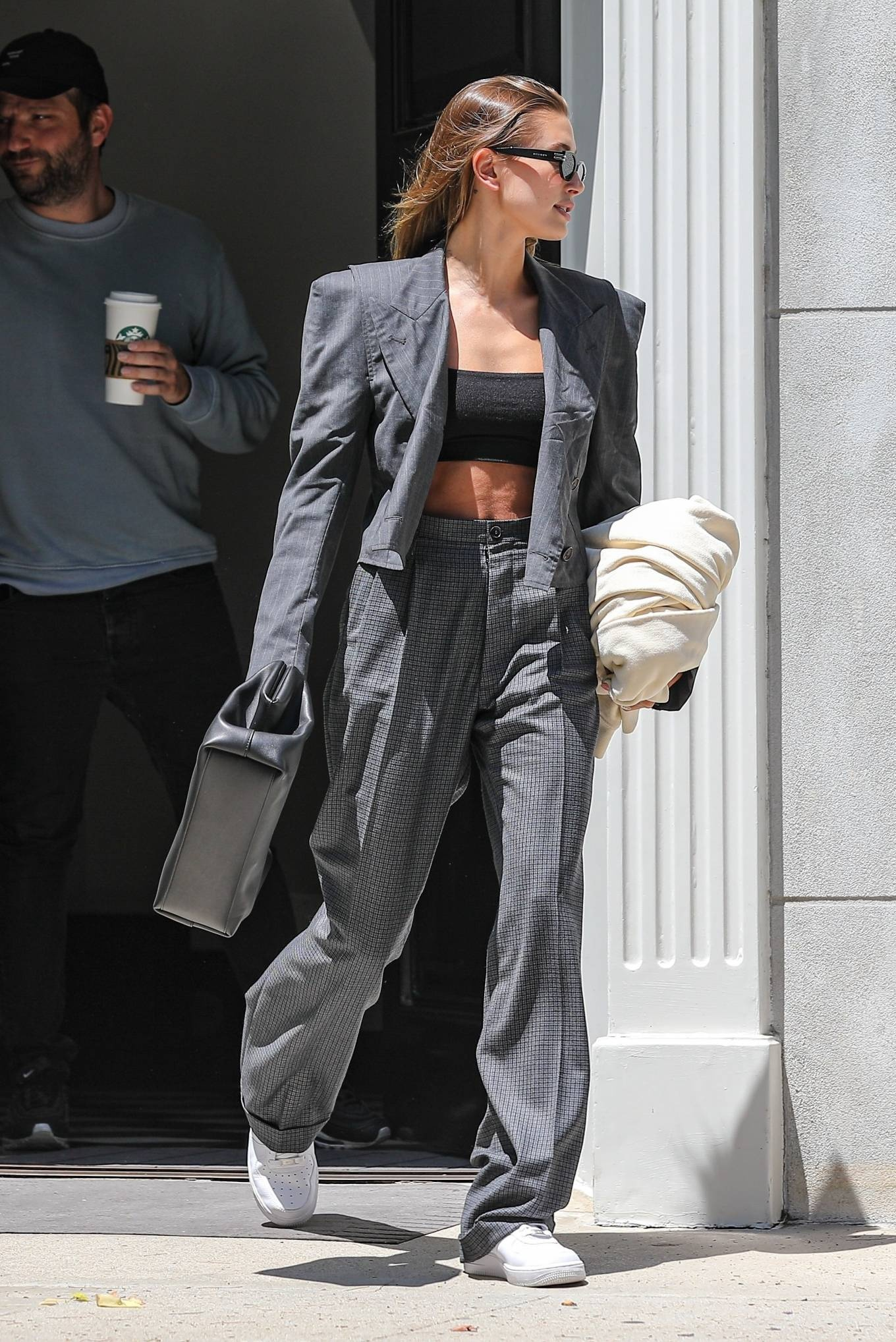 Hailey Baldwin wearing pleated grey woolen trousers with high waist with side pockets