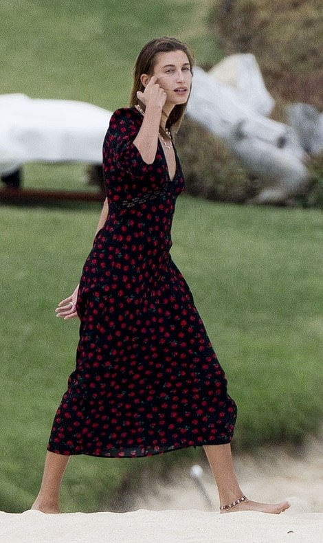 Hailey Baldwin donning a fitted black dress with a viscose fabric, bell sleeves, floral print and a V-neck