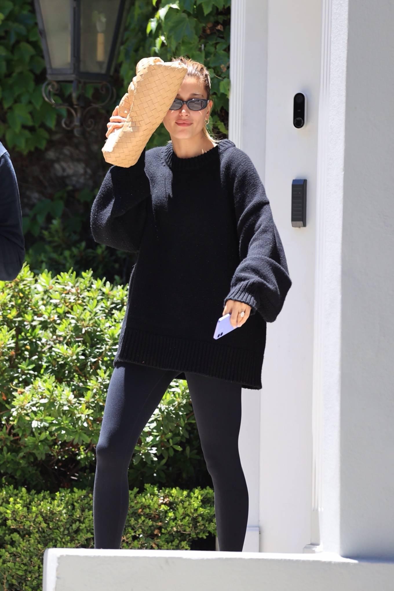 Hailey Bieber wearing round Nude Prada cross strap sandals