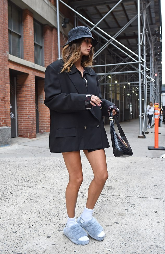 Hailey Bieber rocking a oversized black button up double breasted blazer with long sleeves, peak lapel collar and flap pockets