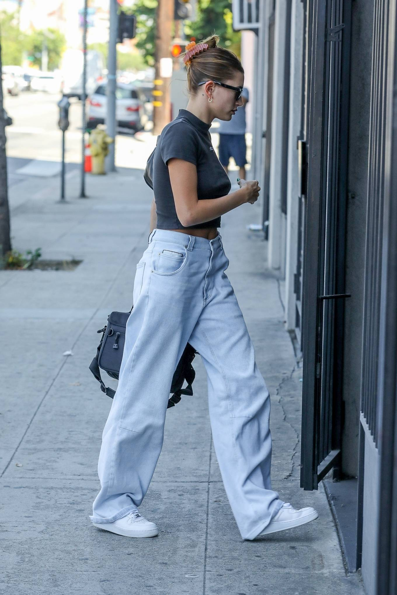 Hailey Baldwin wearing a fitted black crop top with a cotton fabric, short sleeves, brand logo and a high neck