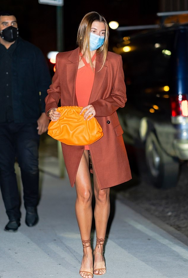 Hailey Baldwin donning a figure hugging orange dress with a nylon fabric and a halter neck