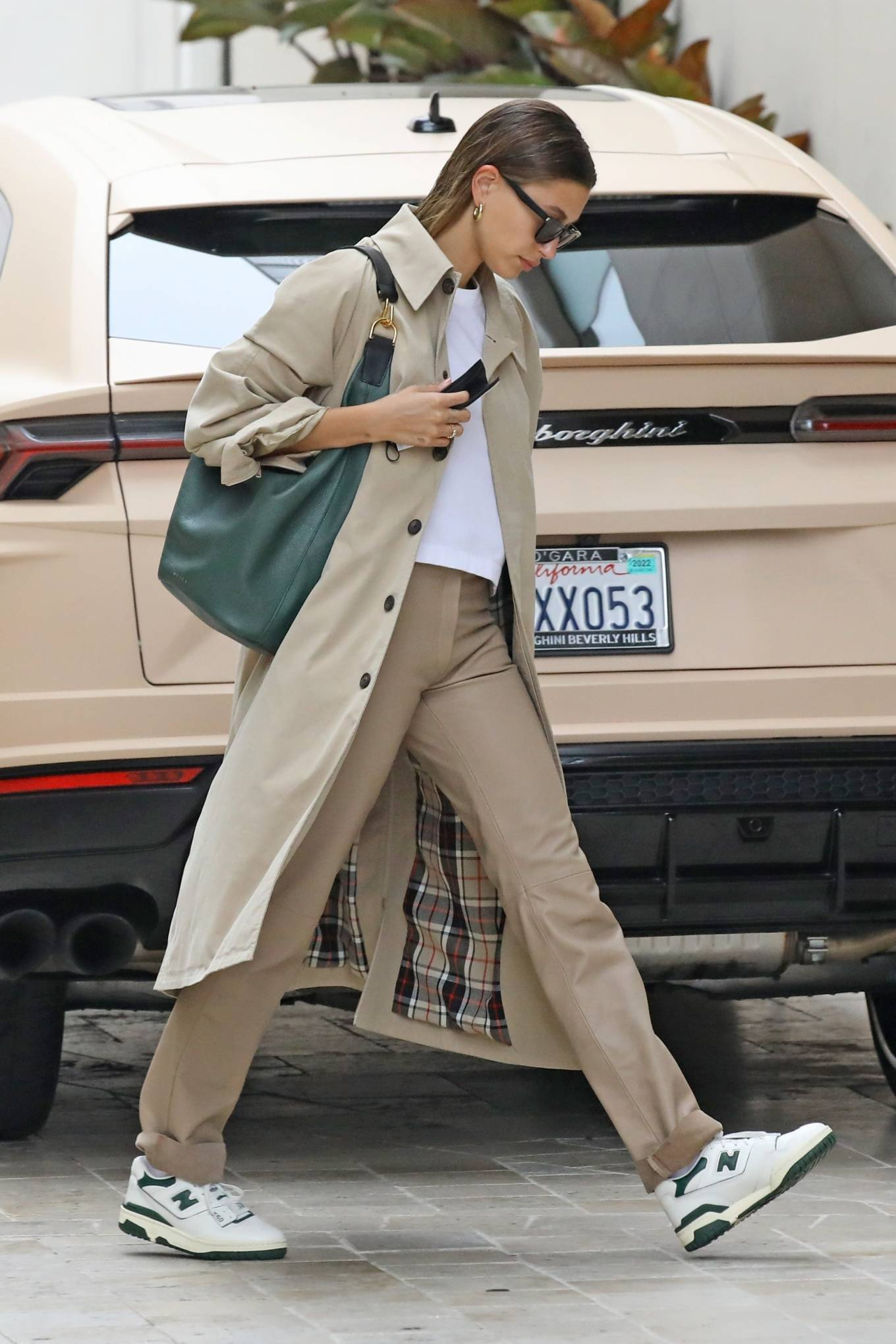 Hailey Bieber donning straight fit beige leather high waist trousers