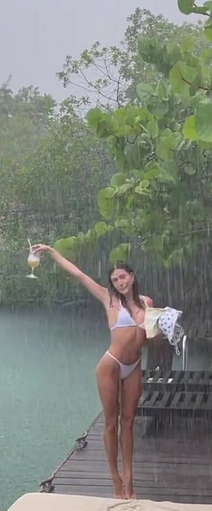 Hailey Bieber wearing a plunging white bikini top with spaghetti straps