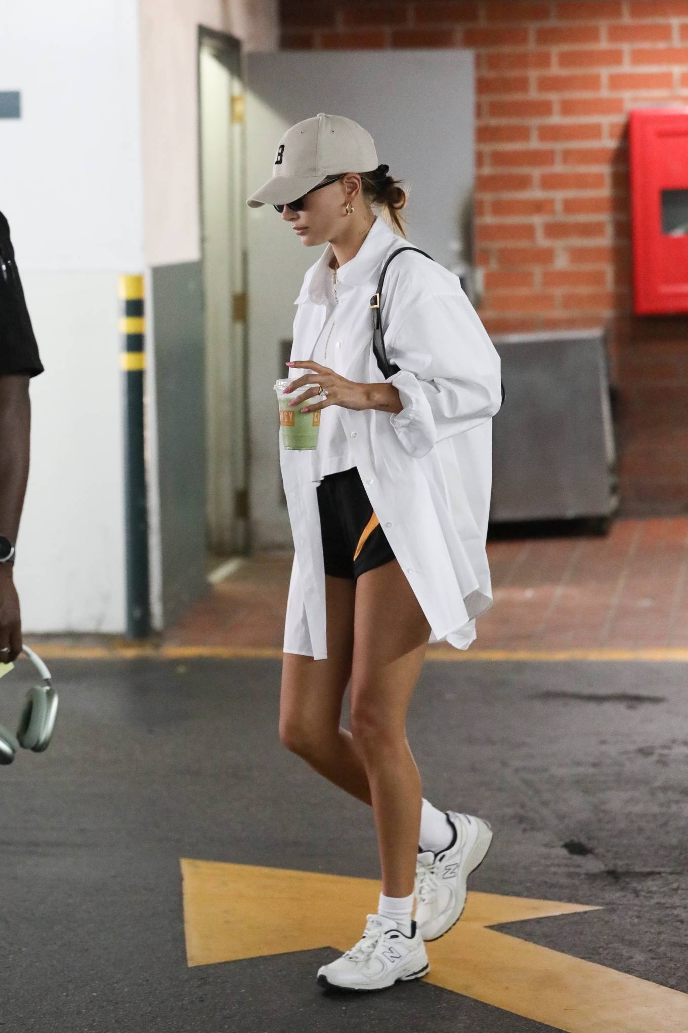 Hailey Baldwin rocking a oversized white open front shirt with rolled sleeves and shirt collar