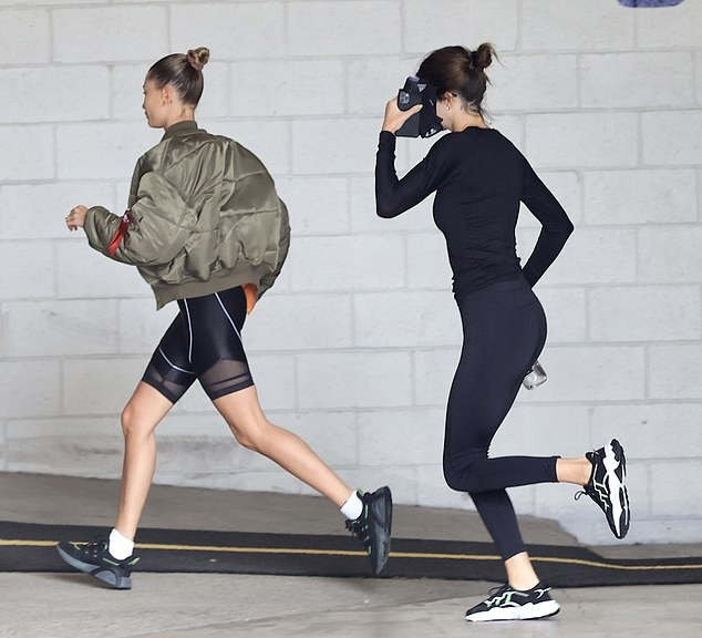 Hailey Bieber wearing Black leather mesh biker shorts with white piping and a leather fabric