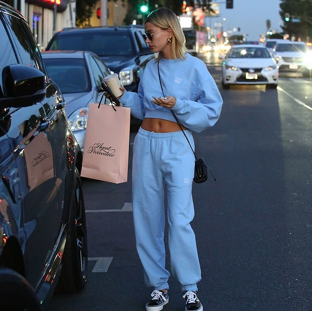 Hailey Bieber donning a oversized Livin Cool crop top with a woolen material, extra long sleeves, a crew neck and ribbed trim hem