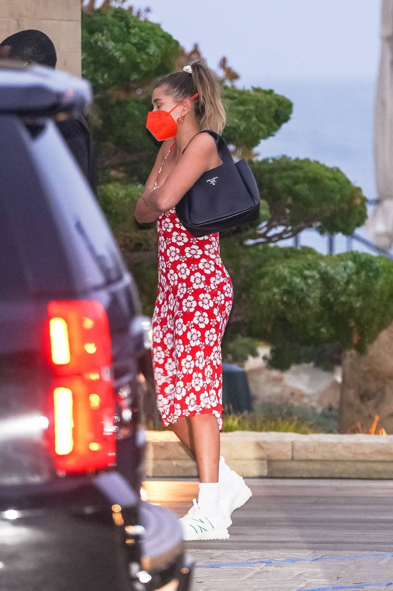 Hailey Baldwin wearing a fitted Holiday The Label dress with a viscose fabric, floral print, a scoop neck and spaghetti straps