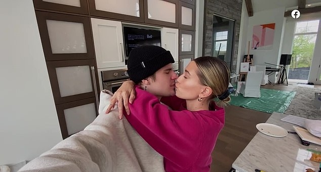 Hailey Bieber wearing a Oversized dark pink Champion cropped sweatshirt with extra long sleeves, embroidered, a crew neck and ribbed trim hem