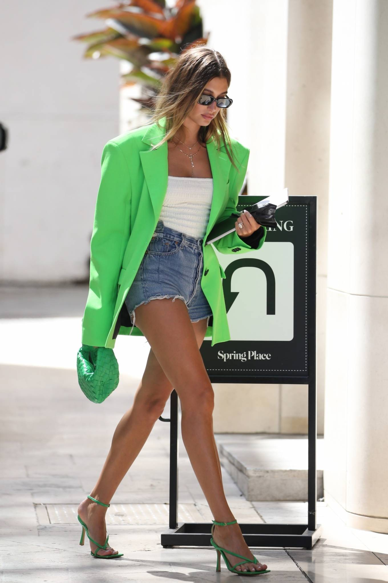 Hailey Baldwin, green sandals, leather, Bottega Veneta sandals, neon green blazer, green Bottega Veneta hand bag, square, ankle, high heel, figure hugging white Toteme camisole, black sunglasses, open toe, thin straps. Hailey Bieber rocking square green Bottega Veneta ankle sandals with high heel and thin straps