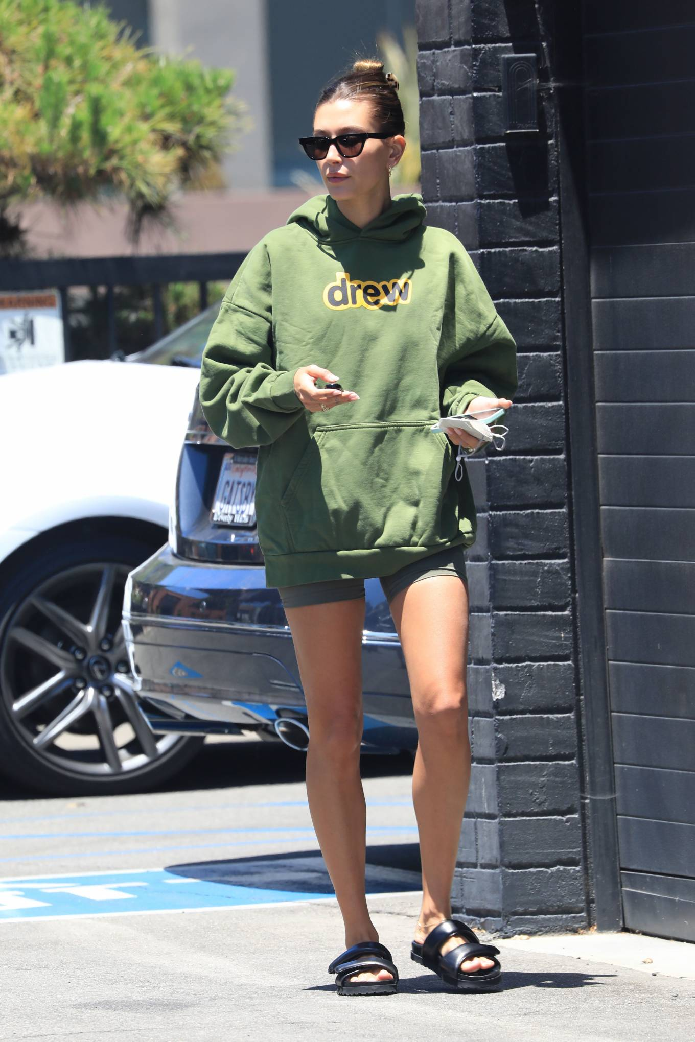 Hailey Baldwin donning round black leather slip on slippers with flat heel