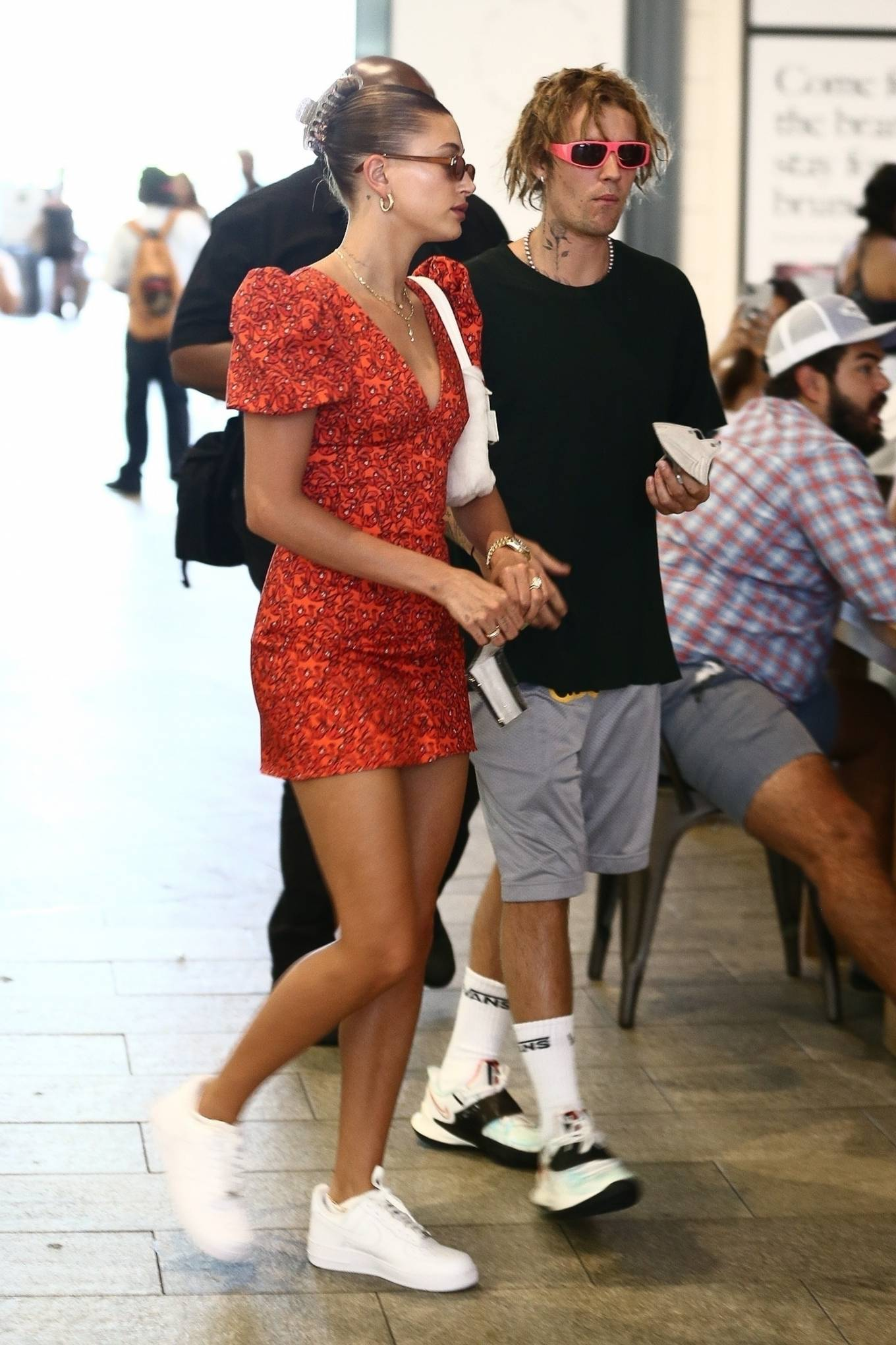 Hailey Baldwin wearing a fitted red dress with a cotton material, bell sleeves, floral print and a V-neck