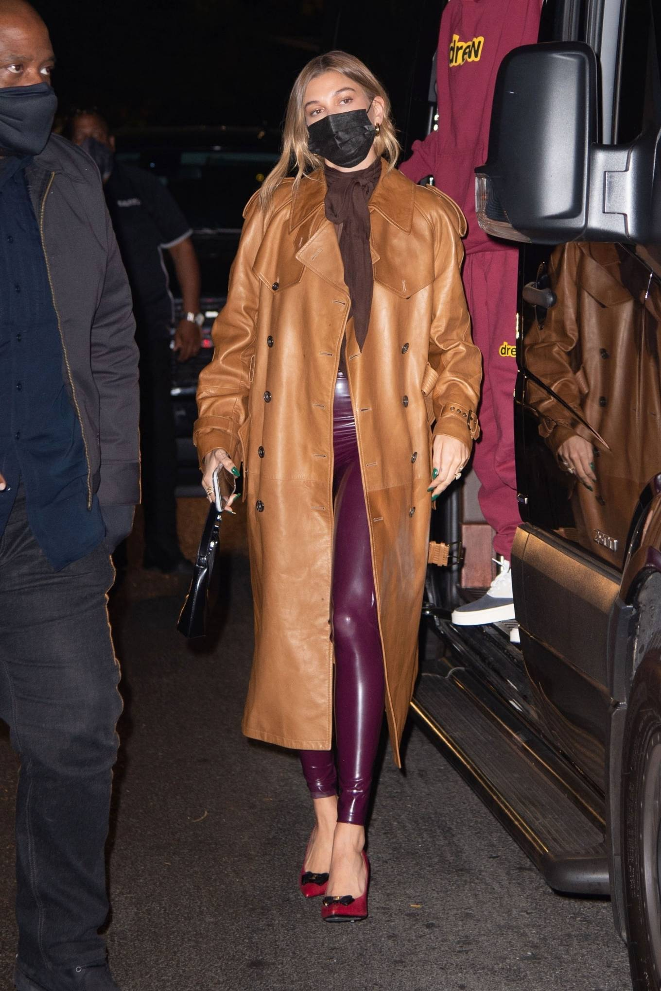 Hailey Baldwin wearing a oversized tan ankle length leather trench coat with extra long sleeves and notched lapel collar