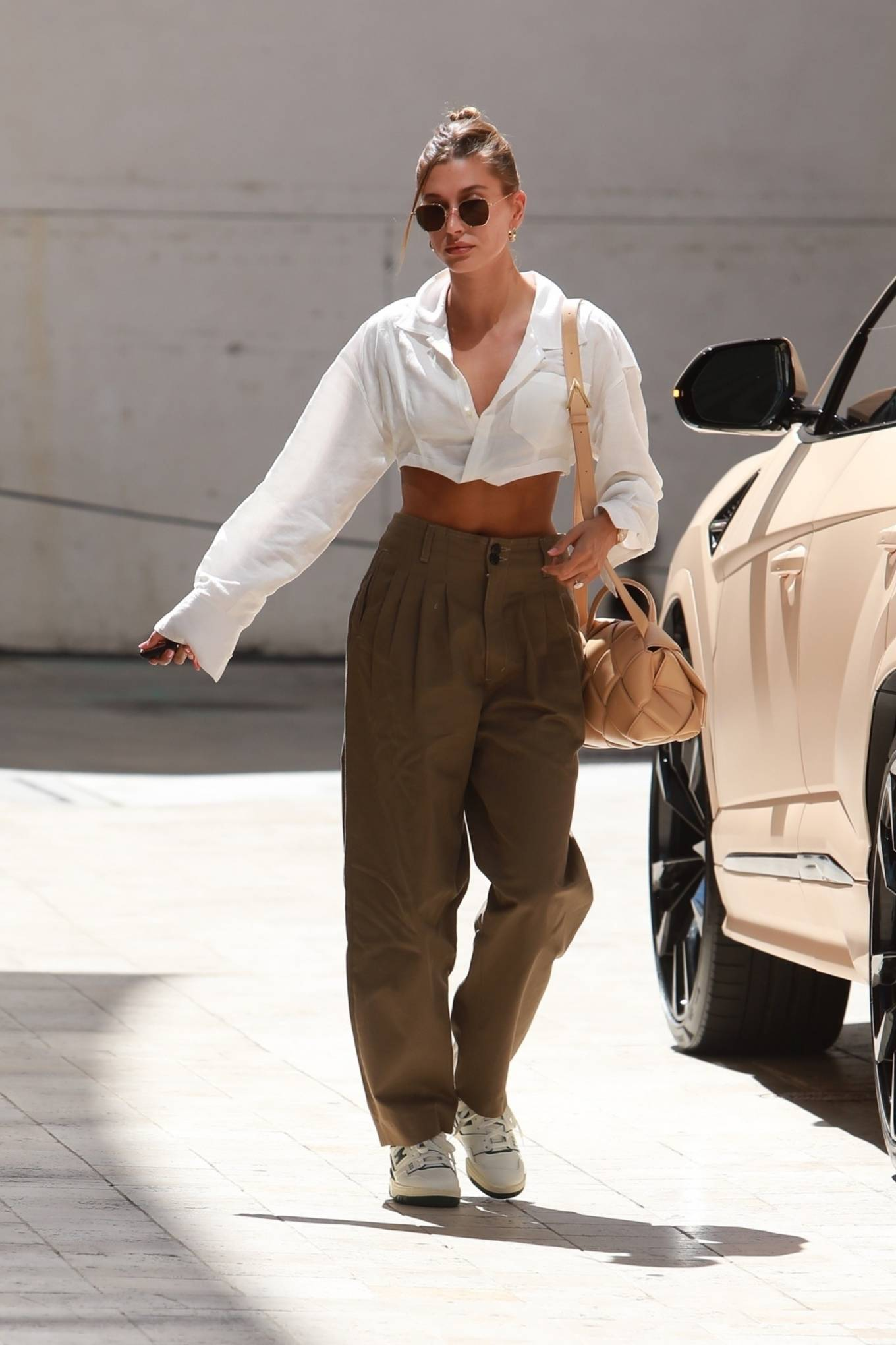 Hailey Bieber wearing brand logo white black lace-up sneakers