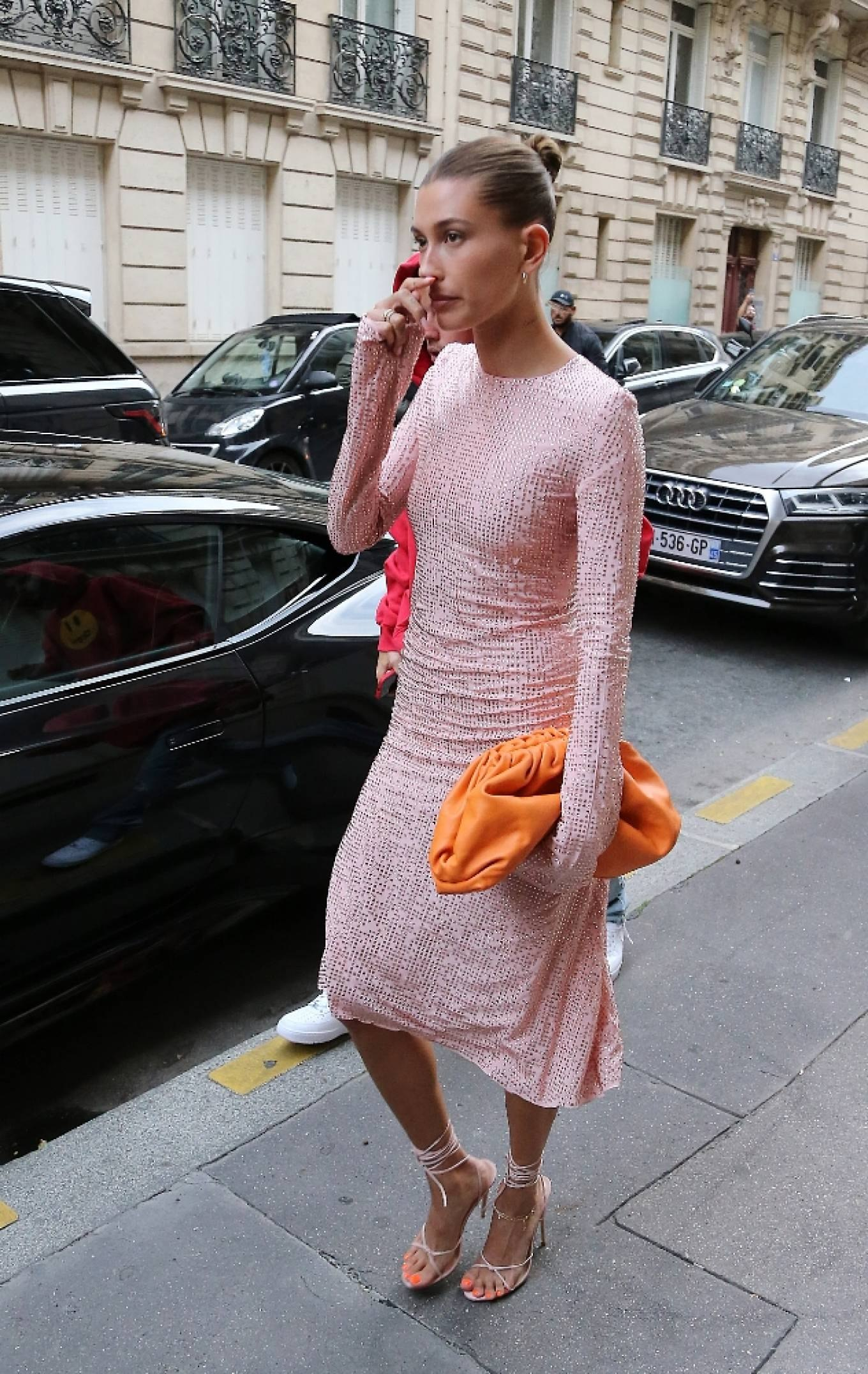 Hailey Baldwin rocking a figure hugging pink dress with full sleeves and a round neck