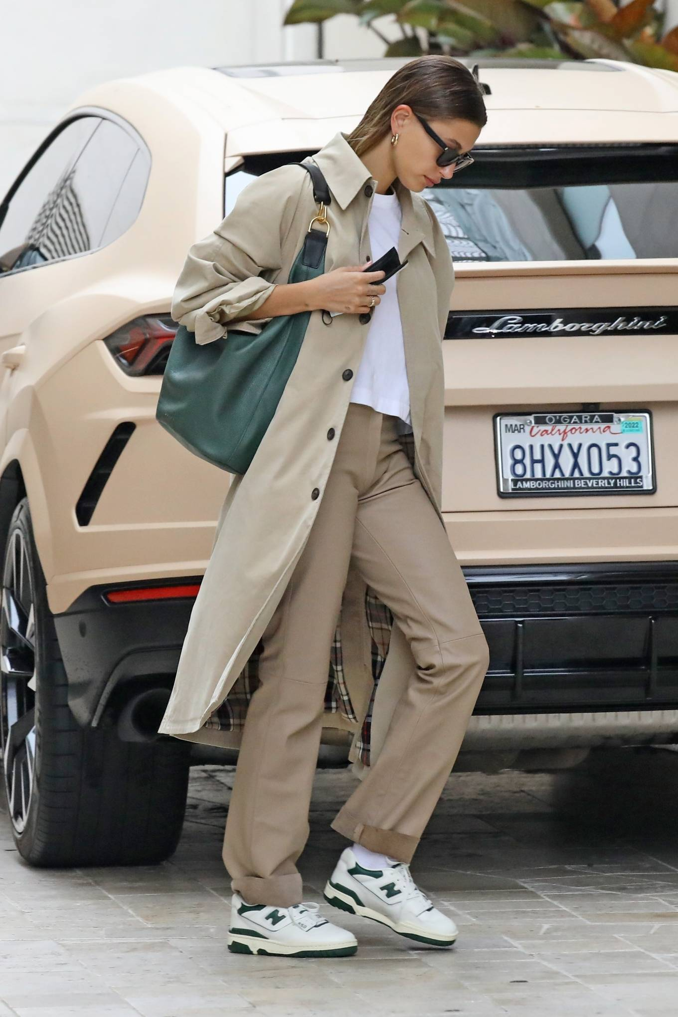 Hailey Baldwin, white sneakers, leather, New Balance sneakers, green shoulder bag, beige Balenciaga trench coat, round, lace-up, brand logo, green sneakers, black Saint Laurent sunglasses, white top, flat heel, beige trousers. Hailey Bieber wearing brand logo white green lace-up sneakers by New Balance with flat heel