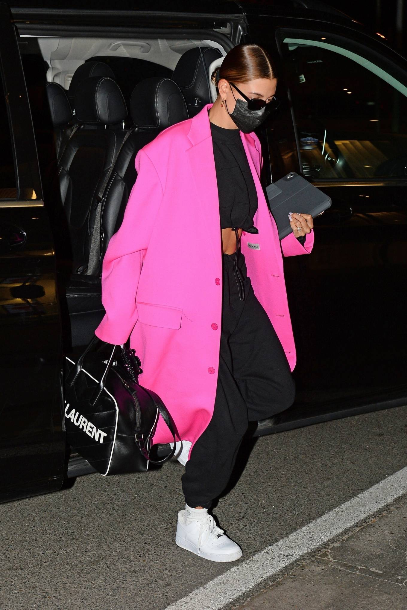 Hailey Bieber wearing a oversized hot pink button front trench coat with extra long sleeves, peak lapel collar and flap pockets