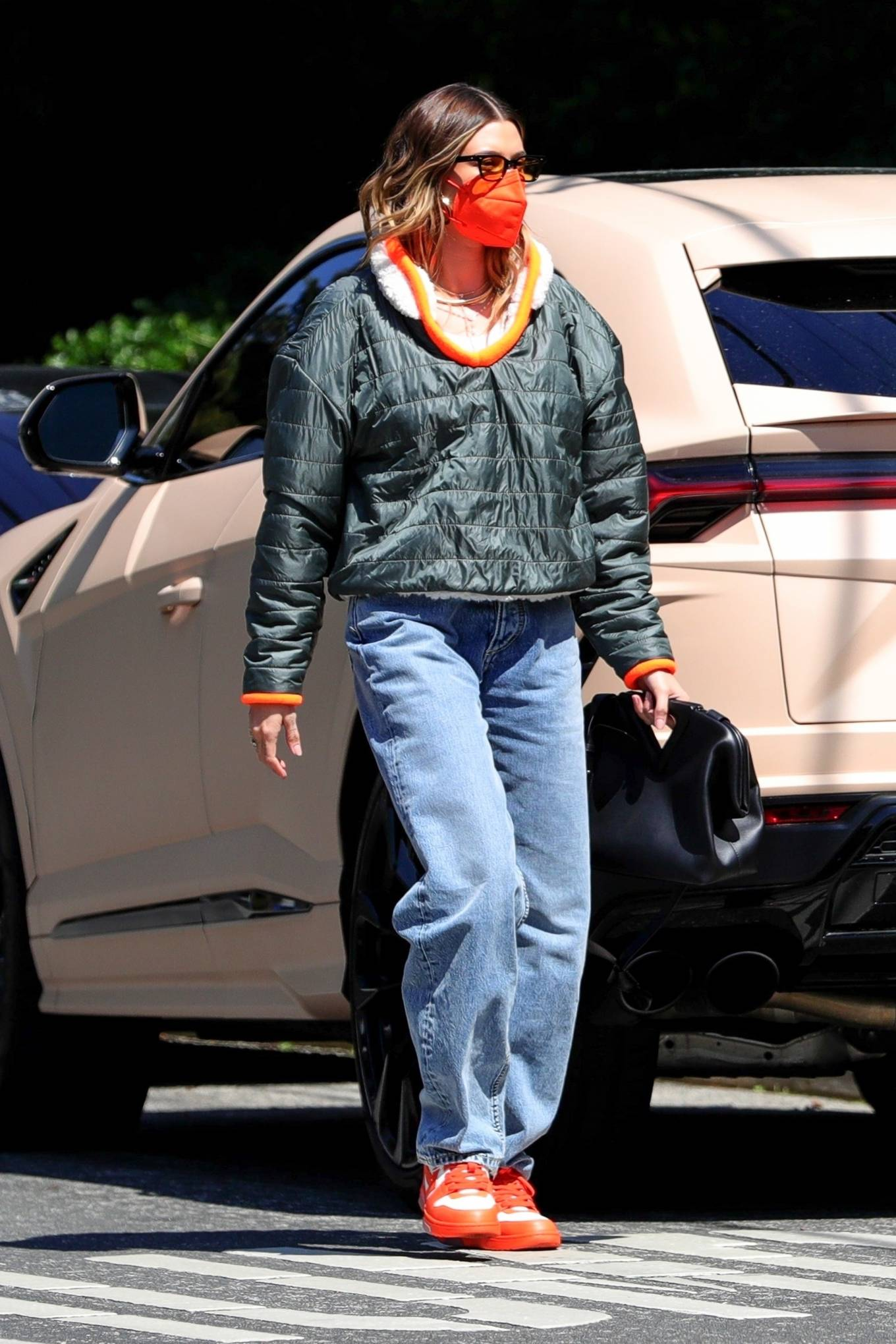 Hailey Baldwin, Nike sneakers, orange and white sneakers, metallic grey pullover, black Bottega Veneta clutch, round, lace-up, brand logo, light blue jeans, yellow sunglasses, color block. Hailey Baldwin wearing brand logo orange and white Nike lace-up sneakers