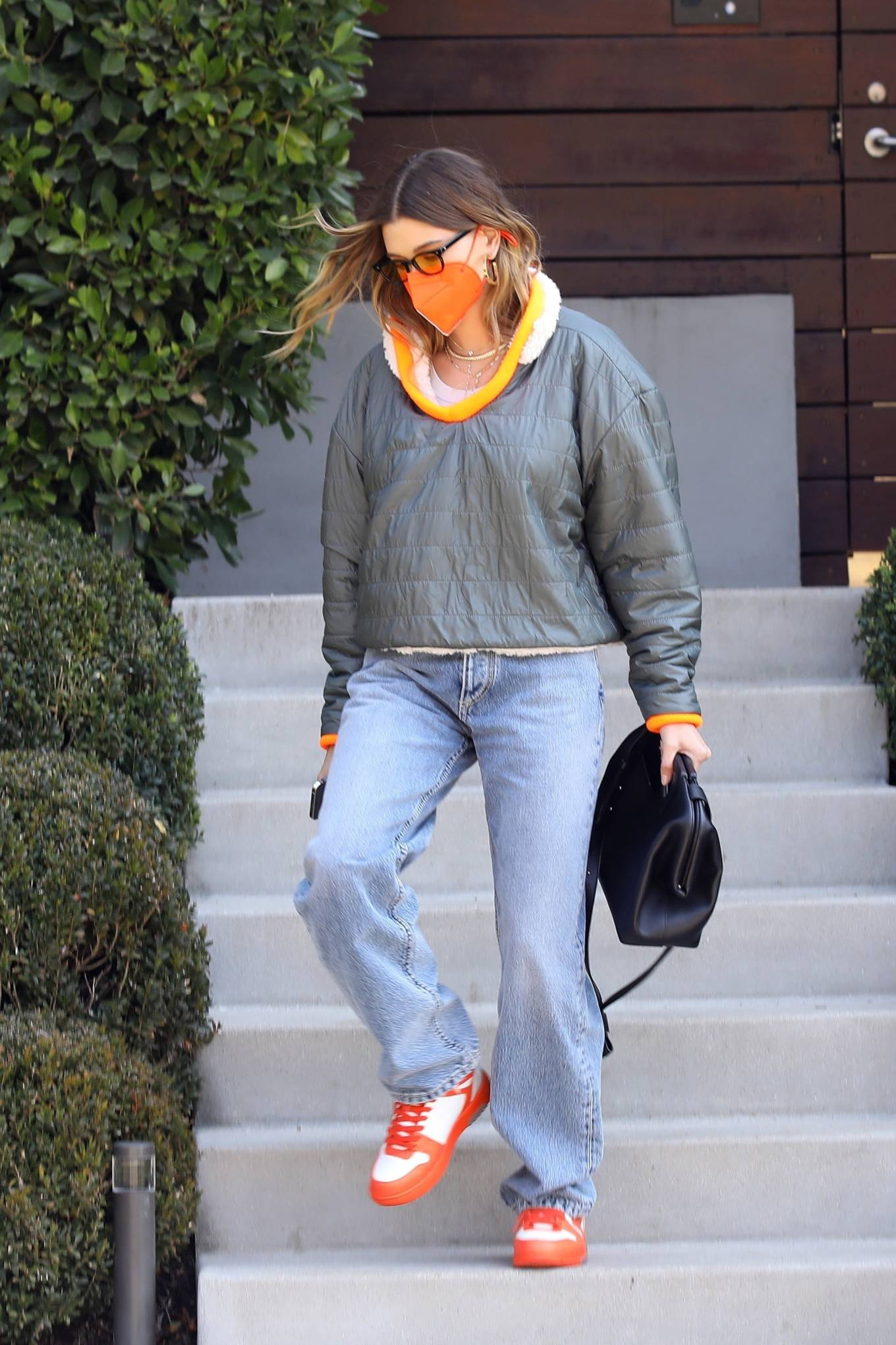 Hailey Baldwin, Nike sneakers, orange and white sneakers, black Bottega Veneta clutch, metallic grey pullover, round, lace-up, brand logo, yellow sunglasses, light blue jeans, color block. Hailey Baldwin wearing brand logo orange and white Nike lace-up sneakers
