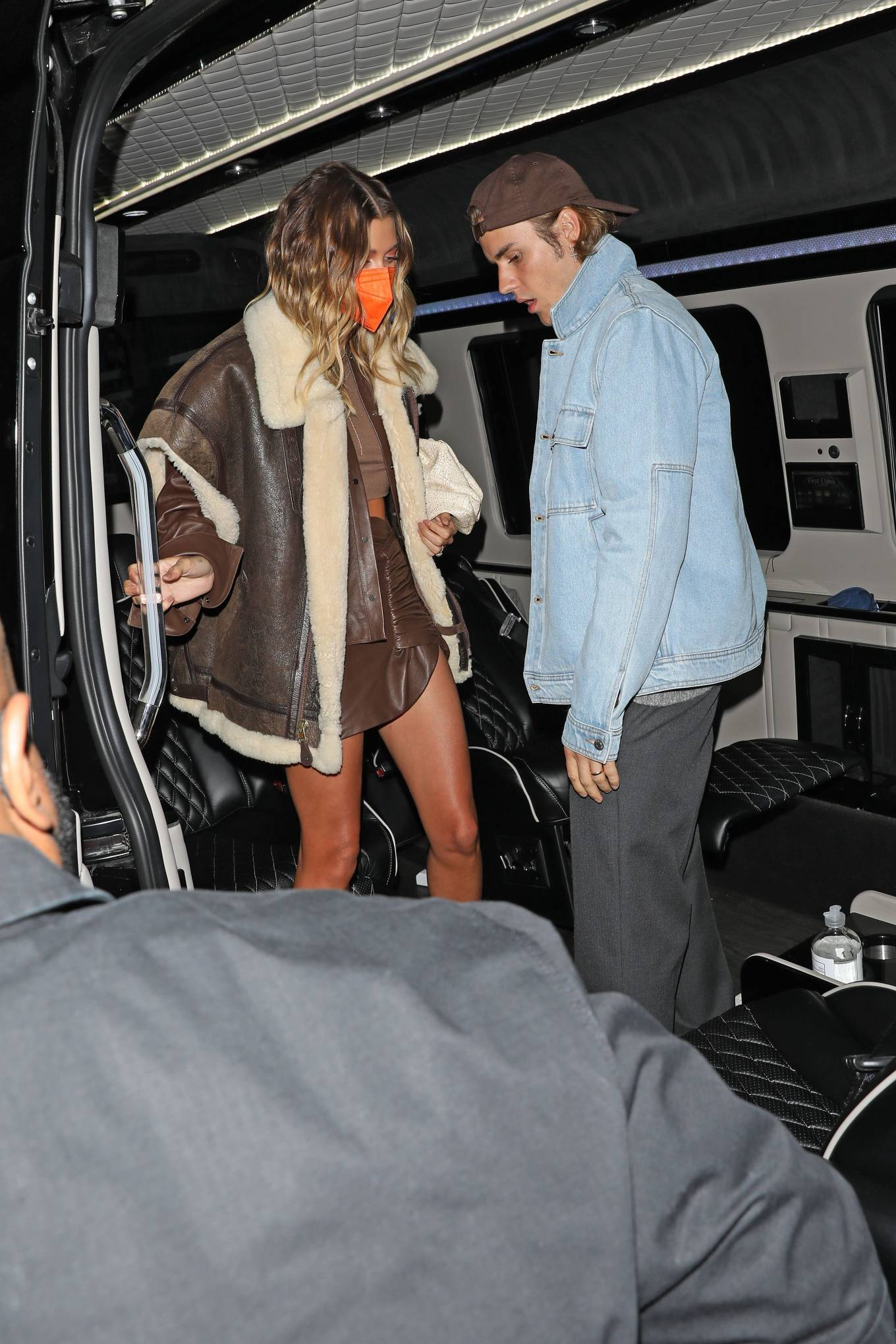 Hailey Baldwin donning a oversized brown strappy leather jacket with a fleece fabric and lapel collar