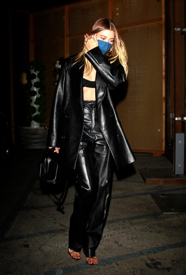 Hailey Bieber wearing relaxed fit shiny black leather high waist trousers