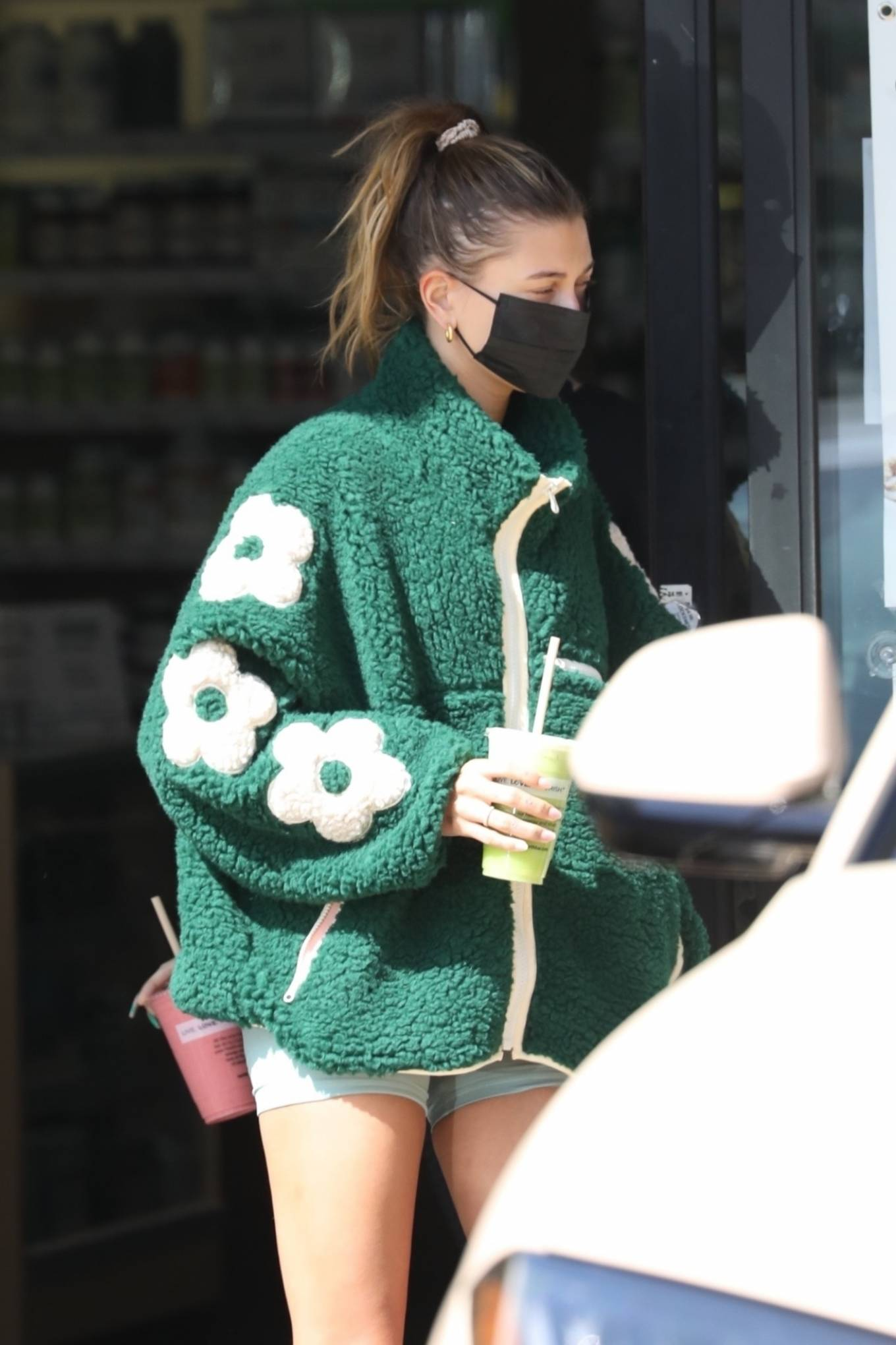 Hailey Bieber wearing a oversized green floral jacket with a fleece fabric, full sleeves and a funnel neck