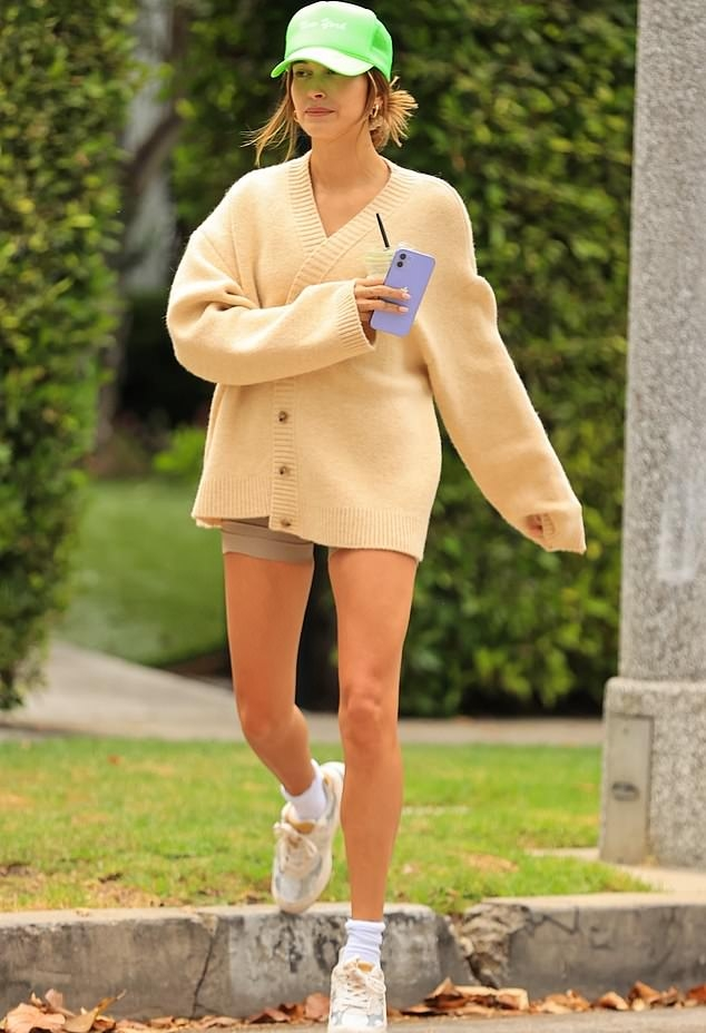 Hailey Baldwin donning a oversized beige button front woolen cardigan with long sleeves and a V-neck