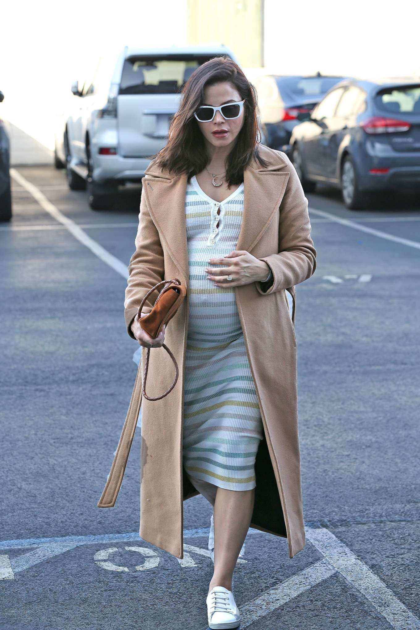 Jenna Dewan wearing a figure hugging white dress with striped and a V-neck