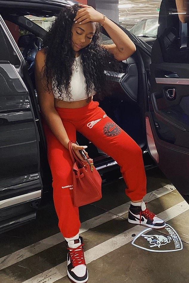 Jordyn Woods donning white black lace-up sneakers by Nike