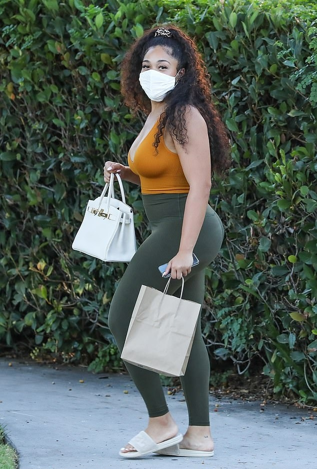Jordyn Woods wearing cream slip on sandals