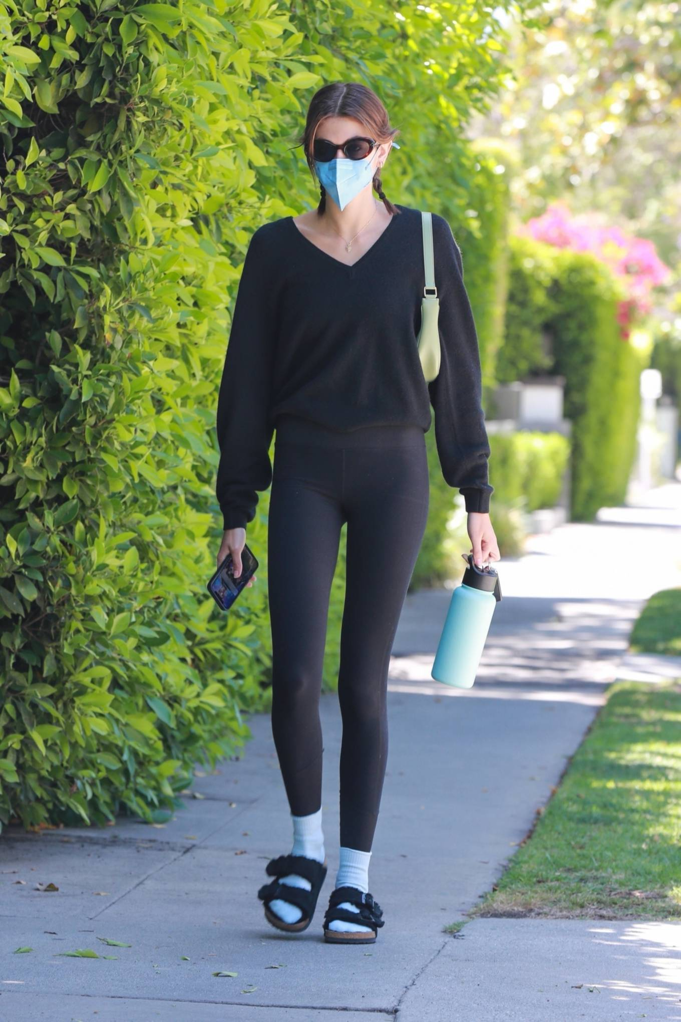 Kaia Gerber wearing a fitted black top with full sleeves and a V-neck