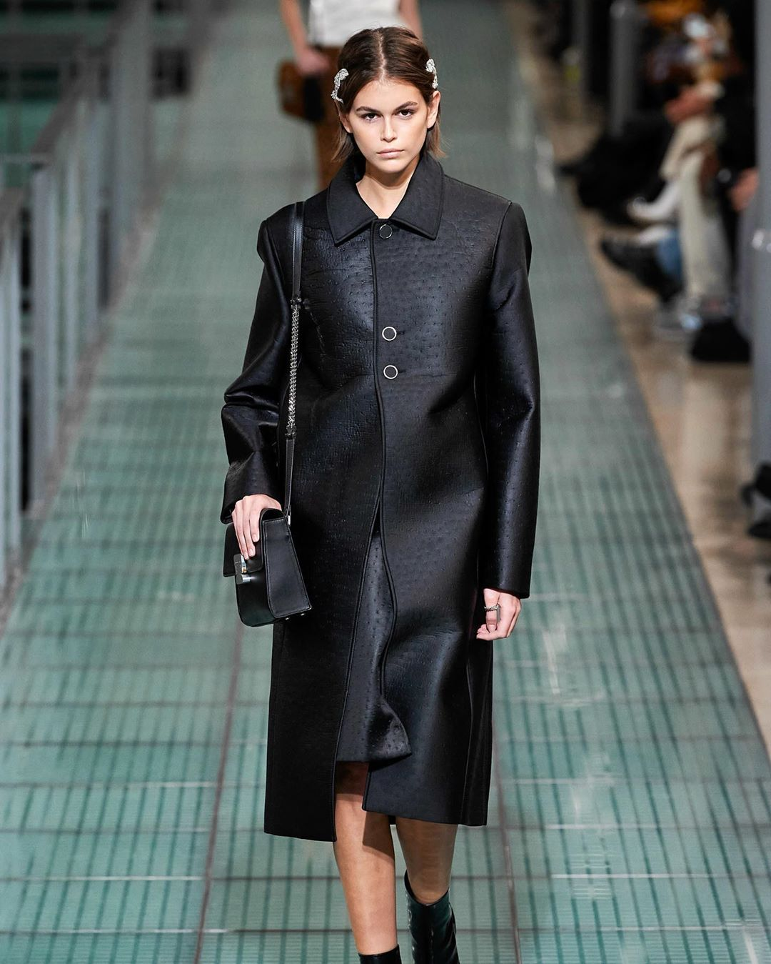 Kaia Gerber donning a menswear inspired black button front leather coat with extra long sleeves, padded shoulder and shirt collar