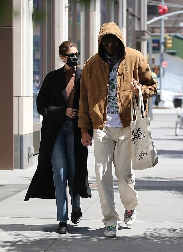 Kaia Gerber wearing a oversized black open front trench coat with full sleeves, lapel collar and side pockets