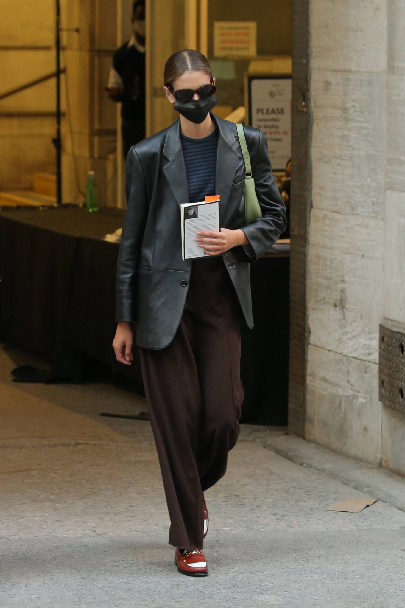 Kaia Gerber wearing narrow brown leather loafers by Celine with flat heel