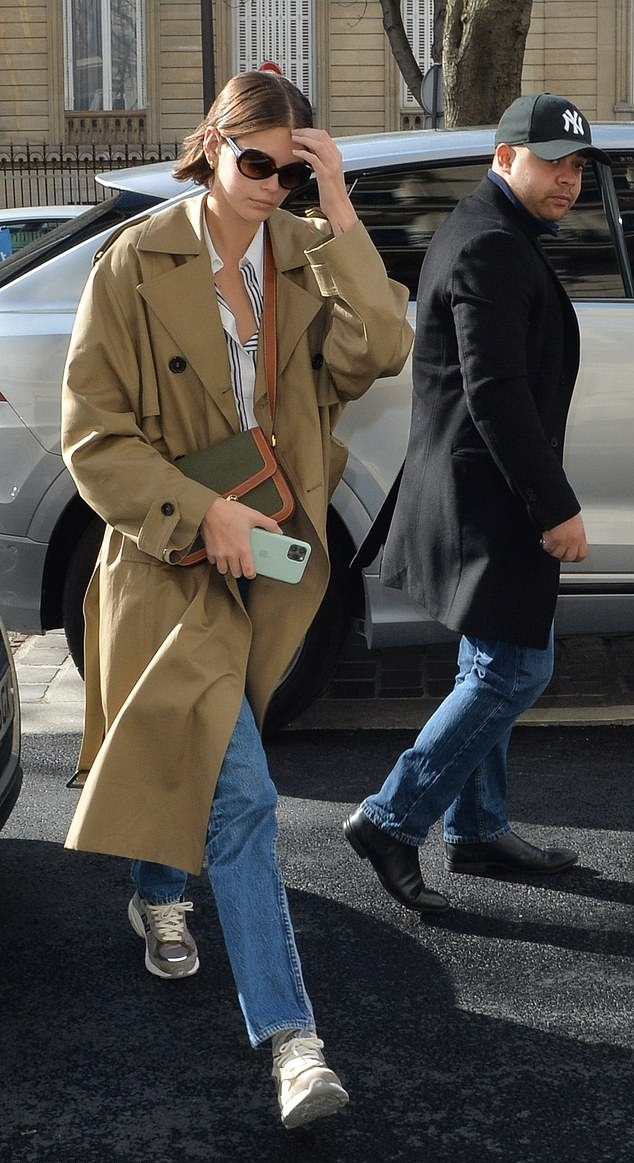 Kaia Gerber wearing a oversized camel button front double breasted trench coat with extra long sleeves, peak lapel collar and flap pockets