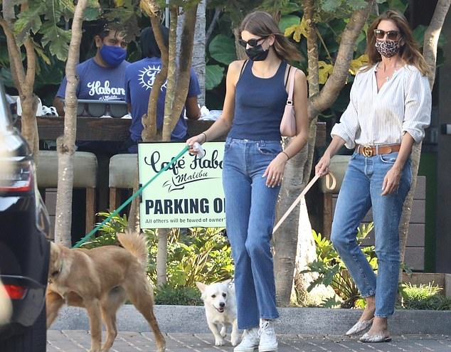 Kaia Gerber rocking brand logo white Converse ankle canvas shoes with flat heel