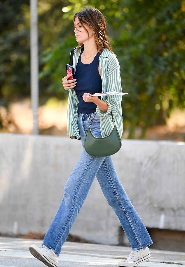 Kaia Gerber rocking brand logo white Converse lace-up high top sneakers