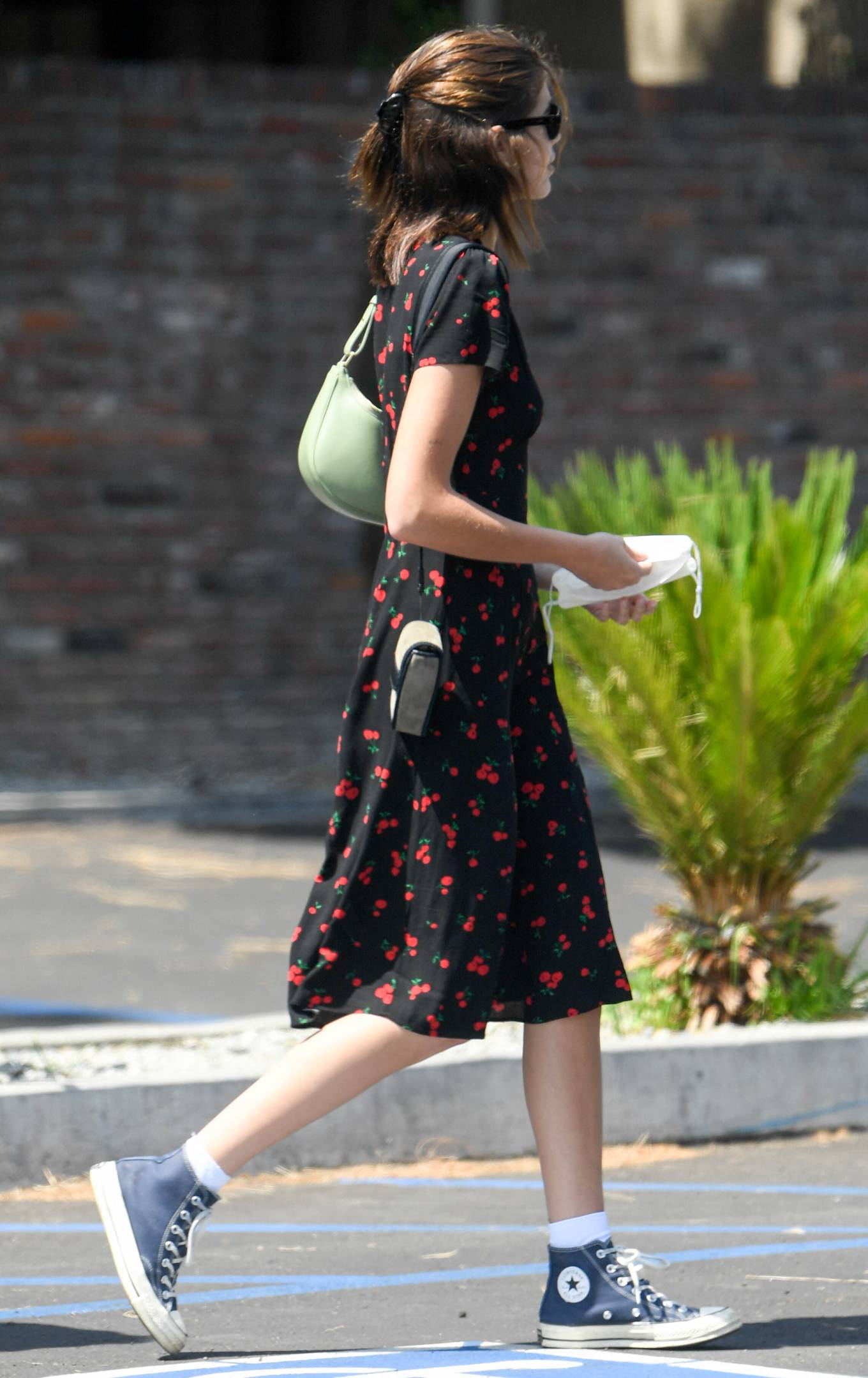 Kaia Gerber wearing a fitted black dress with short sleeves, lapel collar and floral print