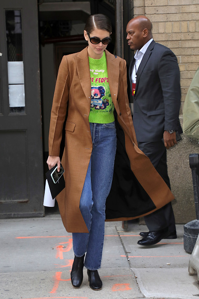 Kaia Gerber wearing a beige button front woolen trench coat with full sleeves, peak lapel collar and flap pockets
