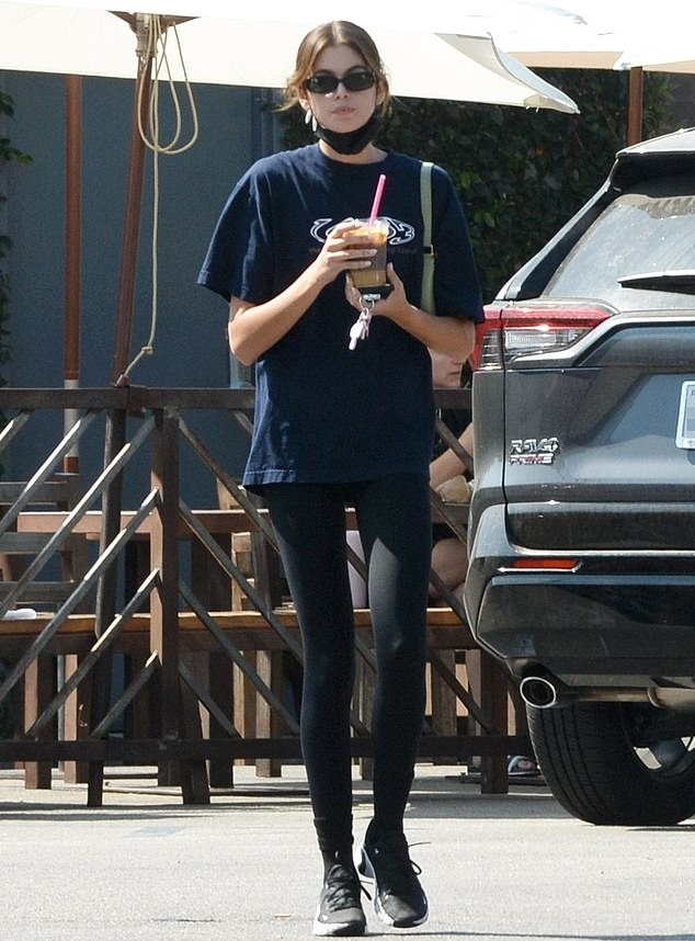 Kaia Gerber wearing round black white lace-up sneakers by Nike with chunky sole