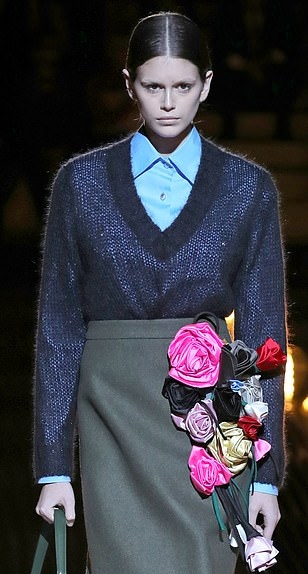 Kaia Gerber wearing a shiny sky blue Prada shirt with full sleeves, shirt collar and button front