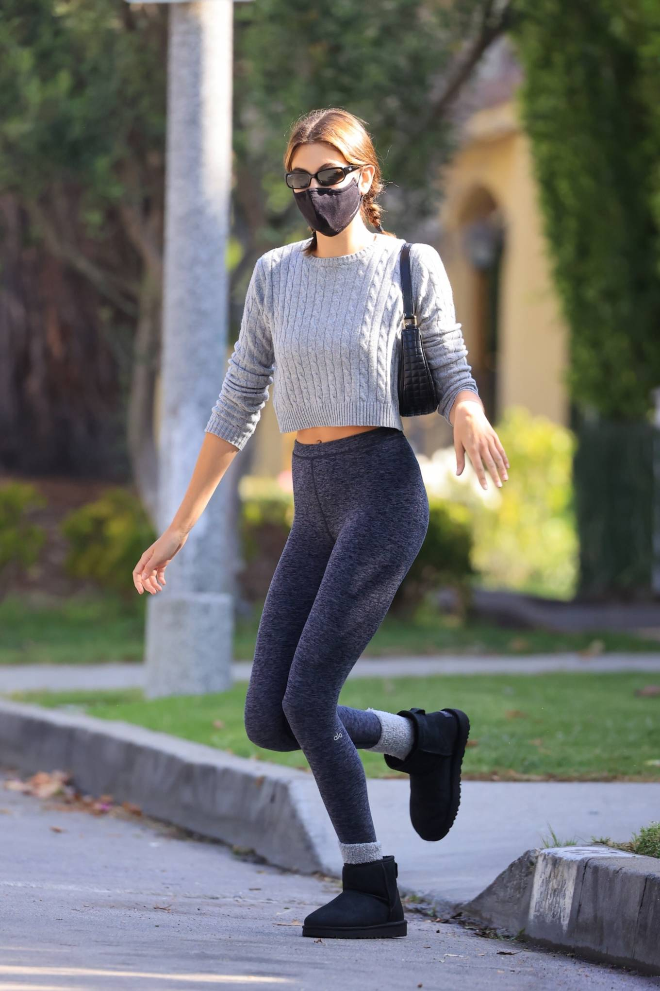 Kaia Gerber, woolen, Brandy Melville sweater, grey sweater, black Ugg boots, grey Alo Yoga workout leggings, rolled sleeves, crew neck, cropped, midriff, pattern, knit, stomach length, black Celine shoulder bag, fitted, black Ray Ban sunglasses. Kaia Gerber donning a fitted grey sweater with a woolen fabric, rolled sleeves, pattern and a crew neck