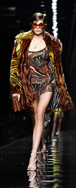 Kaia Gerber wearing a oversized striking brown open front Versace fur reversible coat with extra long sleeves, wide collar and striped